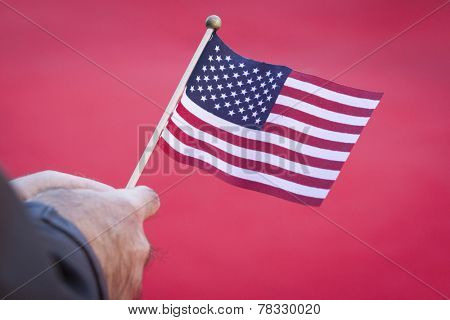 NEW YORK - NOV 11, 2014: Close up of a veterans hand holding a small American Flag during the 2014 Americas Parade held on Veterans Day in New York City on November 11, 2014.