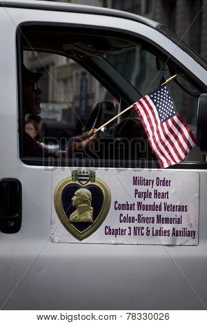 NEW YORK - NOV 11, 2014: A vet waves a small American Flag from the window of the Military Order of the Purple Heart vehicle in the 2014 America's Parade on Veterans Day in New York City.