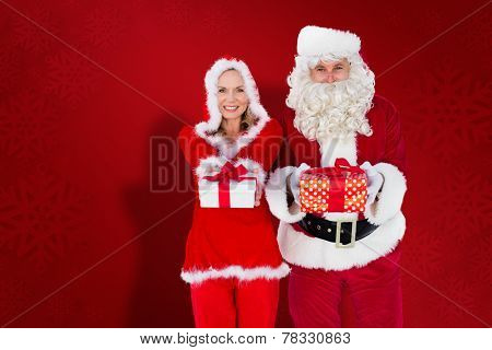 Santa and Mrs Claus smiling at camera offering gift against red snowflake background