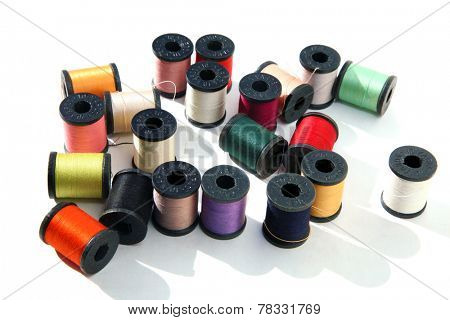 Beautiful Colorful spools of thread isolated on white with room for your text. Thread is used around the world to sew things together to keep people clothed and warm and in the latest fashion