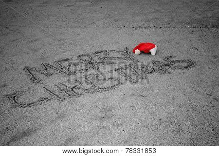The words Merry Christmas written in the sand with a Red Christmas Santa Claus hat next to the word Merry with the Ocean and Seagulls in the background. Christmas is the time many go to the beach