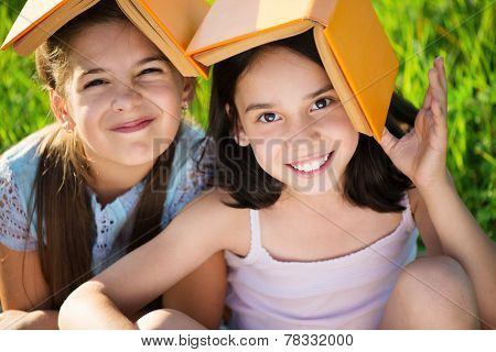 Two Happy Child Girls Studying On Grass