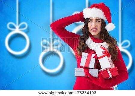 Stressed brunette in santa hat holding gifts against blurred christmas background