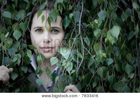 Woman Peering Through Leaves