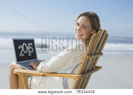 Gorgeous blonde sitting on deck chair using laptop on beach against 2015