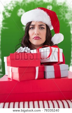 Confused brunette holding pile of gifts against fir trees with snow flakes