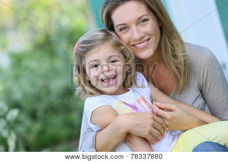 Mother and daughter sitting by house front door
