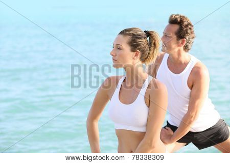 Couple doing yoga and relaxation exercises by the sea