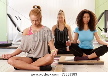 Young women meditating, relaxing at the gym eyes closed.