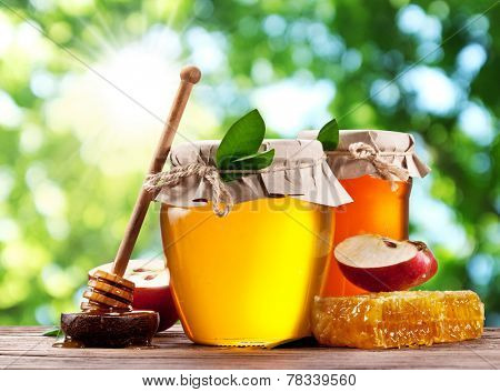 Glass cans full of honey, apple and combs on wooden table at the garden.