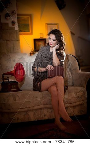 Beautiful young bare feet woman sitting on sofa holding a book having a red gramophone near her