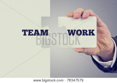 Two Matching Puzzle Pieces With The Word Teamwork Spread Over Them