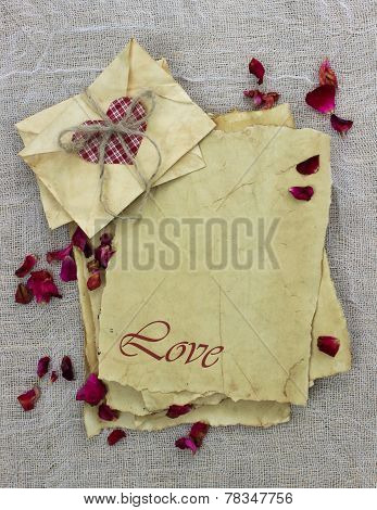 Antique paper love letters and envelopes with red heart and flower petals