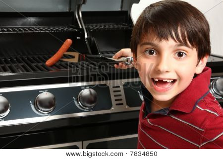 Boy Grilling Up A Hotdog