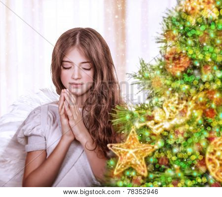 Portrait of little teen angel praying with closed eyes, standing near beautiful decorated Christmas tree at home, waiting for a miracle