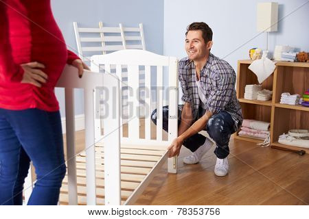 Couple With Pregnant Wife Assembling Cot In Nursery