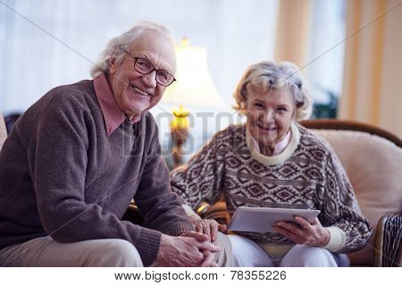 Senior man and his wife looking at camera at home