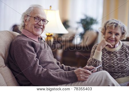 Senior man looking at camera with his wife on background