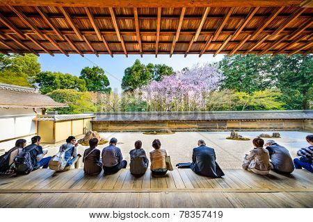 KYOTO, JAPAN - APRIL 9, 2014: Tourists sit and observe the spring cherry trees of Ryoan-ji Temple. The garden is considered one of the finest surviving examples of dry landscapes.