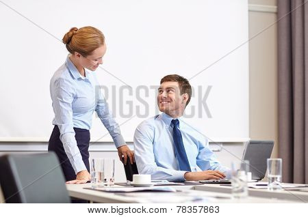 business, people and work concept - businessman and secretary with laptop working in office