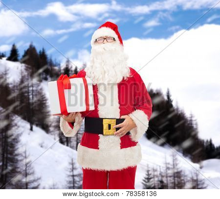 christmas, holidays and people concept - man in costume of santa claus with gift box over snowy mountains background