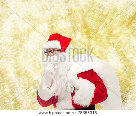 christmas, holidays and people concept - man in costume of santa claus with bag making hush gesture over yellow lights background