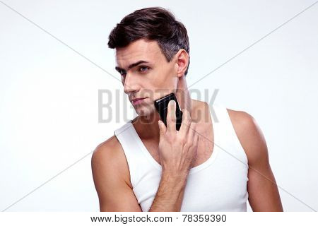 Handsome man shaving with electric razor over gray background