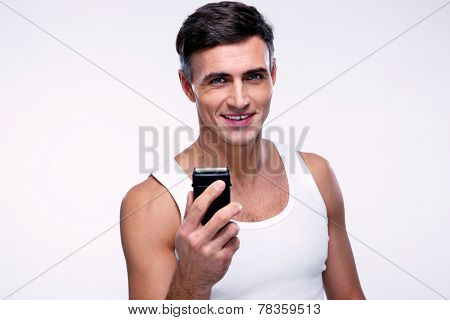Happy man holding electric razor over gray background