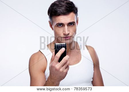 Handsome man holding electric razor over gray background