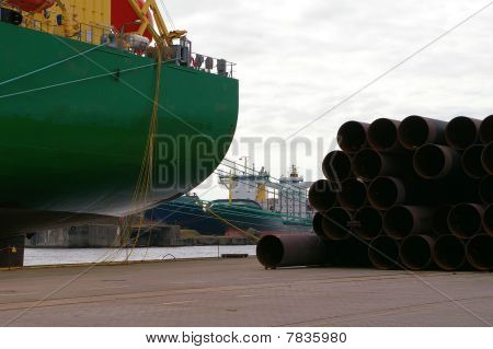 Containerships and huge steel tubes at quay