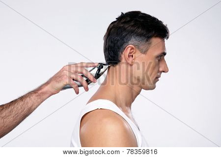 Side view portrait of a man cuts hair with hair clipper on back of the head