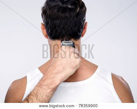 Closeup portrait of a man cuts hair with hair clipper on back of the head