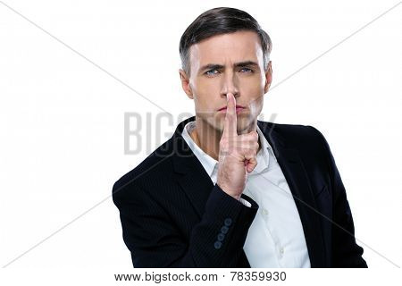 Businessman placing finger on lips saying shhh, be quiet!