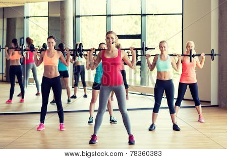fitness, sport, training, gym and lifestyle concept - group of women with barbells in gym