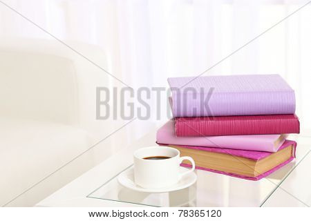 Purple books with cup near sofa on tabletop on the light window background
