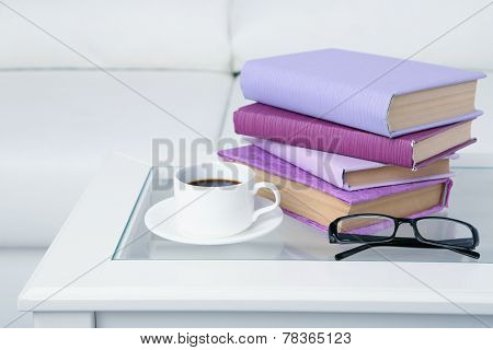 Purple books with cup and glasses on the tabletop on sofa background