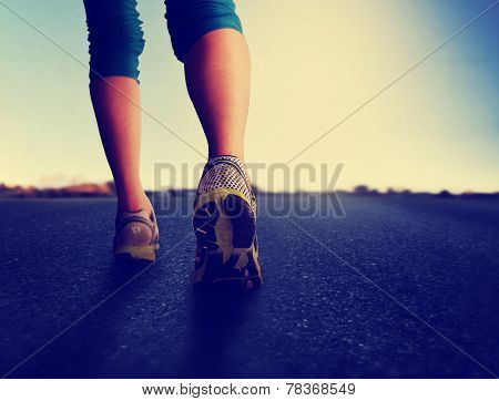 a woman with an athletic pair of legs going for a jog or run during sunrise or sunset - healthy lifestyle concept done with an instagram like filter