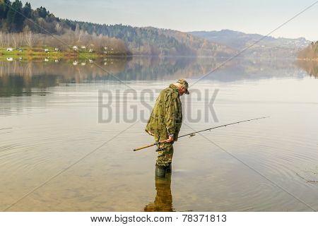 Senior fisherman fish in Solina Lake, Bieszczady, Poland