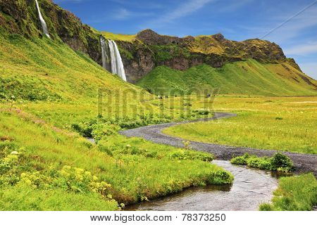 Iceland in July. Warm summer day. Selyalandfoss waterfall and picturesque flowering fields and streams