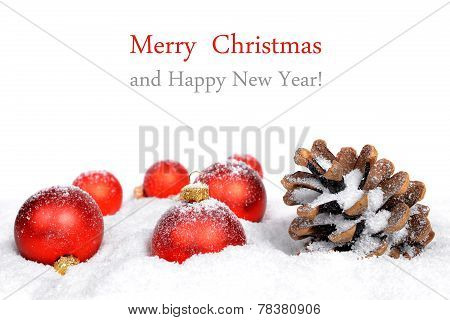 Christmas decorations and pine cones in snow.