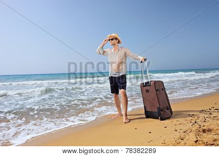 Lost young tourist with his baggage on a sandy beach by the ocean