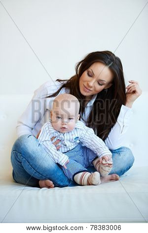 Pretty Smiling Mom with Long Black Hair Sitting on White Couch with her Cute Bald Baby Boy. Isolated on White Background.