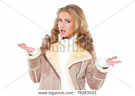 Stylish young woman with gorgeous long curly blond hair wearing a trendy jacket shrugging her shoulders with a puzzled expression to show she does not know and is ignorant