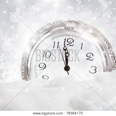 New Year's at midnight - Old clock in the snow against holiday lights