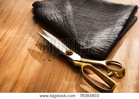 Tailor's work table. textile or fine cloth making.Gold scissors and black silky fabric.