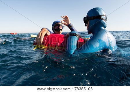 Split shot of two free divers training in sea with buoy