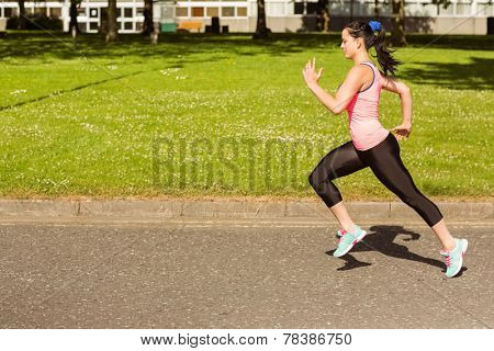 Fit brunette going faster on path in the park on a sunny day
