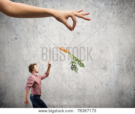Young man in casual teased by carrot hanging on rope