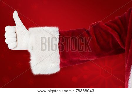 Father Christmas gives a thumb up against red background