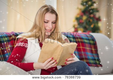 Pretty blonde reading book at christmas time against twinkling stars